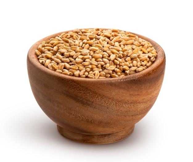 Chicchi di grano in ciotola di legno isolata su fondo bianco