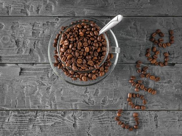 Chicchi di una tazza di caffè e iscrizione del caffè su una tavola di legno. la vista dall'alto. disteso. cereali per la preparazione della bevanda popolare.