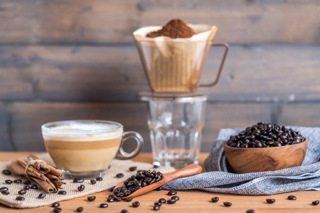 Chicco di caffè e caffè caldo con la tazza di caffè immergere sul tavolo di legno.