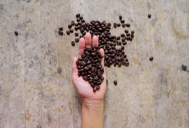 Chicco di caffè in mano su legno vecchio
