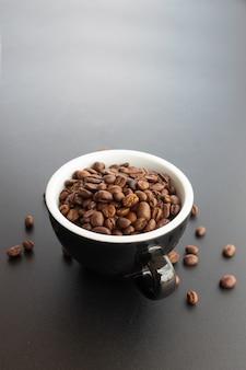 Chicco di caffè in tazza su sfondo nero