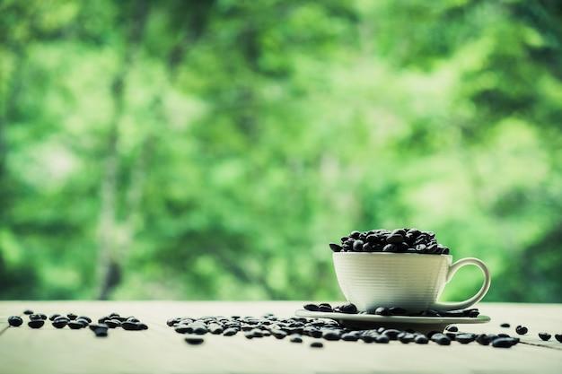 Chicco di caffè in tazza sulla tavola di legno nello sfondo naturale