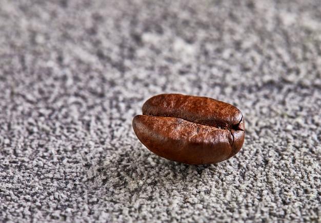 Chicco di caffè profumato con ombra su uno spazio concreto.