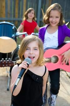 Chidren ragazza cantante che suona dal vivo banda nel cortile