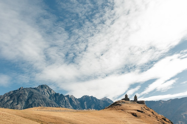 Chiesa della trinità di gergeti conosciuta come tsminda sameba sullo sfondo di un crinale montuoso e nuvole, stepantsminda, kazbegi, georgia.