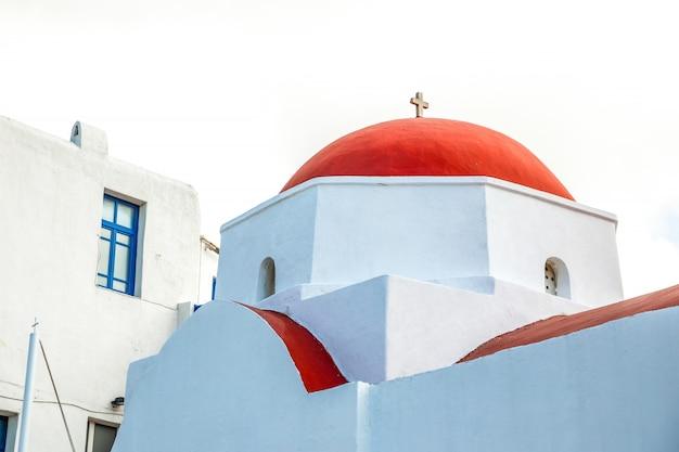 Chiesa di agia kyriaki, edificio bianco tipico della chiesa greca con cupola rossa contro il cielo blu sull'isola di mykonos, in grecia