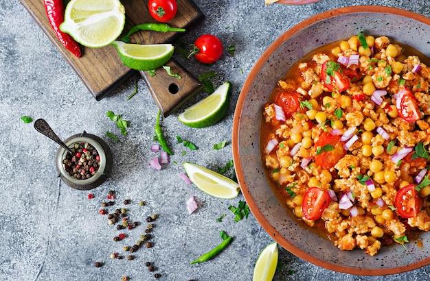 Chili con carne di tacchino con ceci servito con nachos. peperoncino con carne, nachos, lime, peperoncino. cibo tradizionale messicano / texano. vista dall'alto