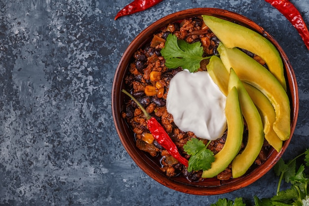 Chili con carne in una ciotola con avocado e panna acida.