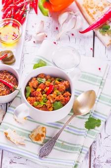 Chili con carne messicano con gli ingredienti sulla tavola di legno bianca.
