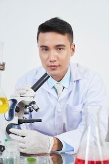 Chimico che lavora con miscroscopio