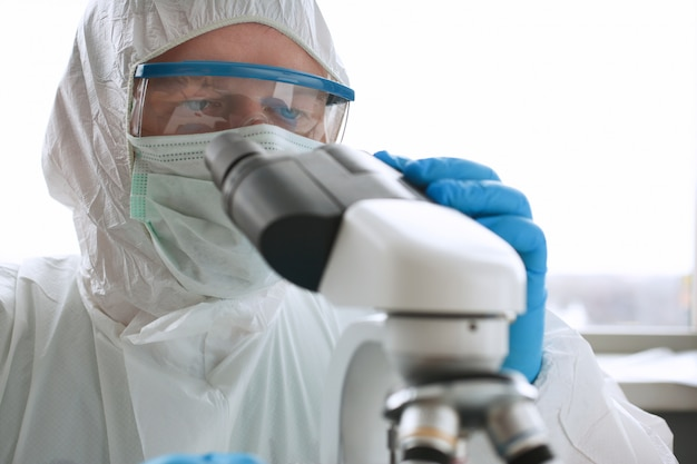 Chimico maschio nello sguardo blu dei guanti protettivi