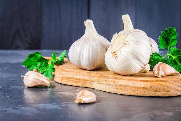 Chiodi di garofano di aglio e lampadina dell'aglio su un bordo di legno su un fondo grigio.