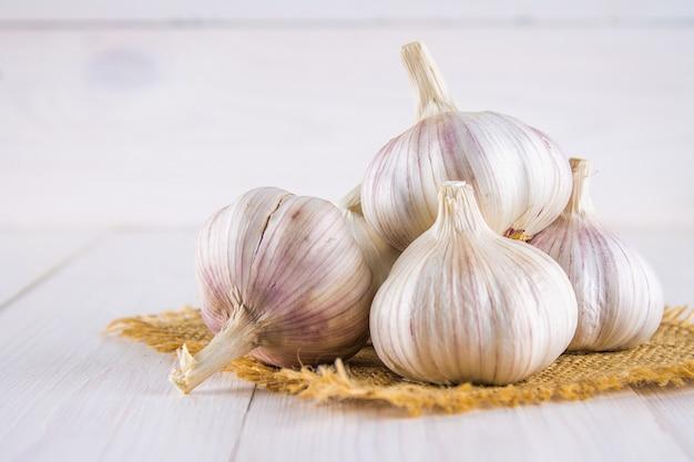 Chiodi di garofano di aglio e lampadina dell'aglio su una tavola di legno bianca