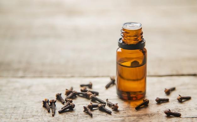Chiodi di garofano olio essenziale in una bottiglietta. messa a fuoco selettiva.