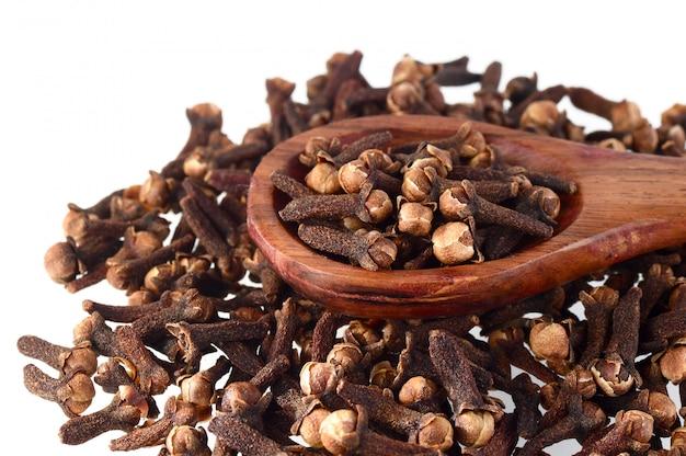 Chiodi di garofano (spezia) e cucchiaio di legno close-up cibo sfondo. isolato su sfondo bianco