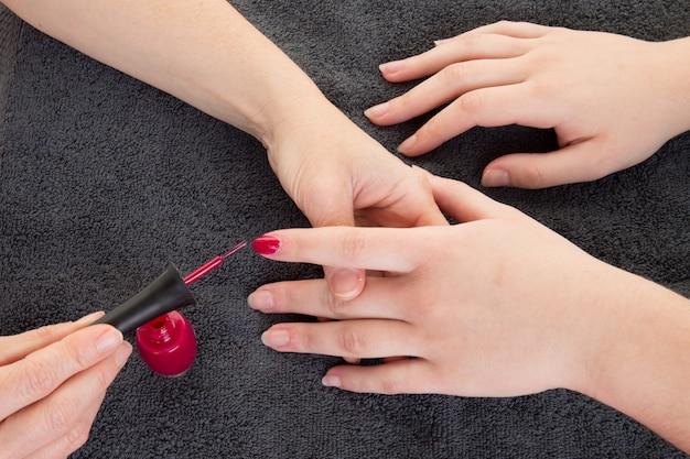 Chiodi di limatura della mano dell'estetista della donna in salone