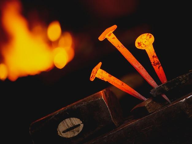 Chiodo caldo del metallo del primo piano per i ferri di cavallo su un'incudine nell'officina del fabbro.