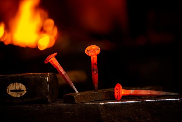 Chiodo caldo del metallo del primo piano su un'incudine nell'officina del fabbro.