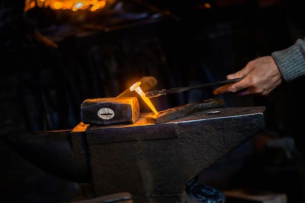 Chiodo di metallo caldo primo piano su un'incudine nella bottega del fabbro