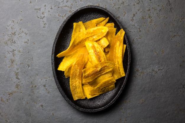 Chip casalinghi sani della piantaggine della banana sulla banda nera