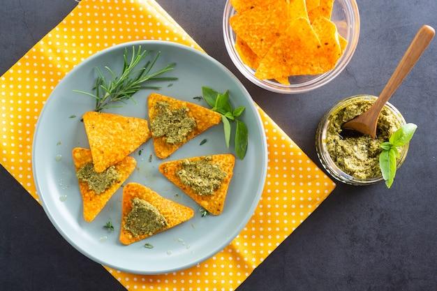 Chip dei nachos o chip messicani del cereale con lo spuntino sano dell'alimento della pasta di pesto, vista superiore