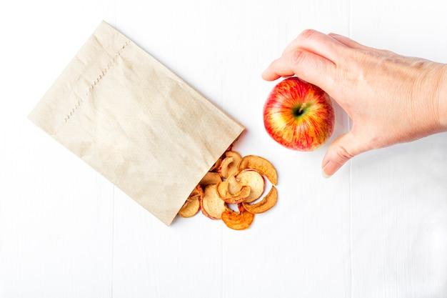Chip di frutta asciutti casalinghi organici in un pacchetto di carta di eco e mele fresche su bianco