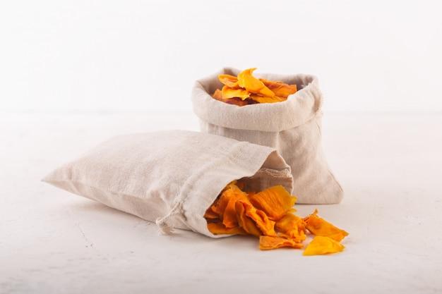Chip di mango in un tessuto borse e pezzi di questo frutto su un tavolo