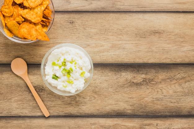Chip di nachos con ciotola di tuffo di formaggio e cucchiaio di legno sul tavolo