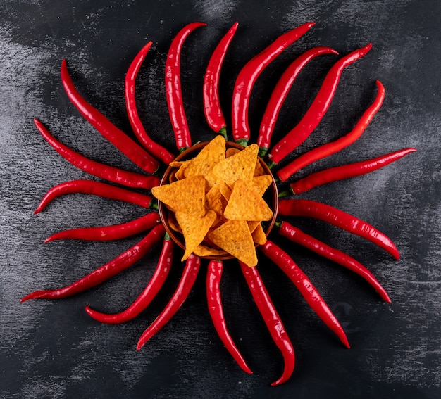Chip di vista superiore con i peperoncini rossi in ciotola sull'orizzontale di pietra nero