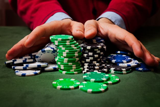 Chip in primo piano, nella sfocatura delle mani di un uomo che tiene fiches, giocando a poker