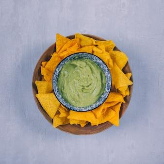 Chip messicani dei nachos con guacamole in contenitore sopra fondo concreto