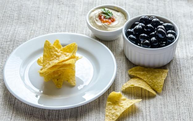Chips di mais con hummus e olive
