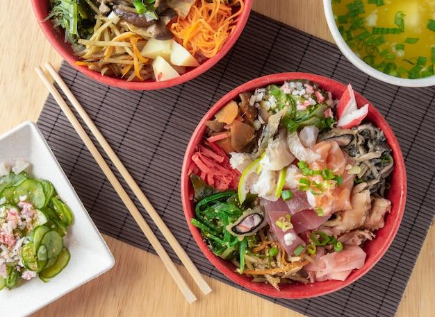 Chirashi di pesce, cibo japonese su ciotole con hashis in legno.