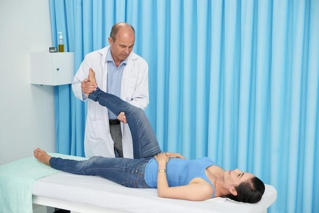 Chiropratica che manipola la gamba del paziente durante la sessione di riabilitazione