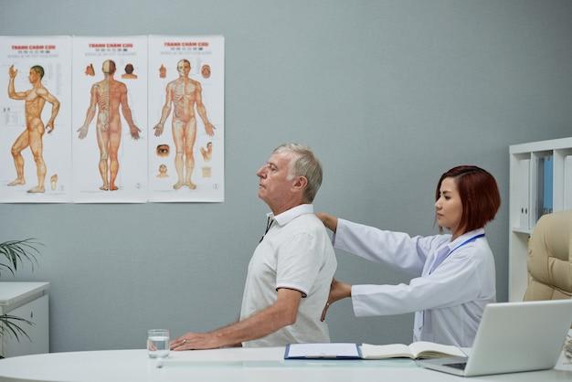 Chiropratico che controlla la colonna vertebrale