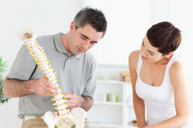 Chiropratico e paziente guardando un modello di una colonna vertebrale