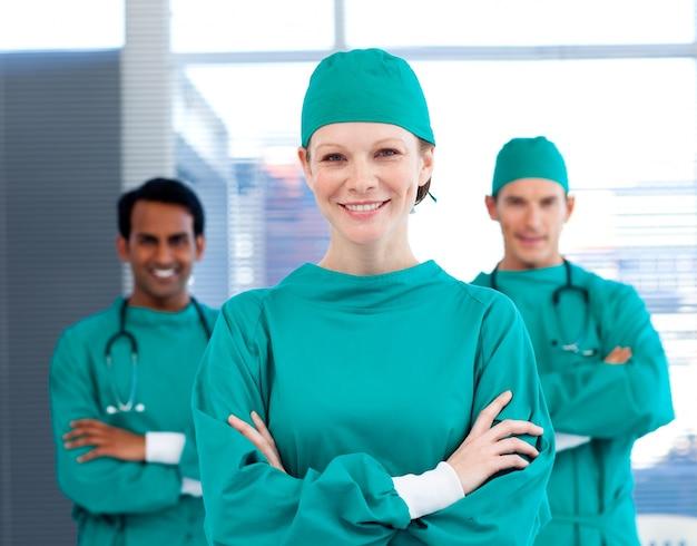 Chirurghi positivi con le braccia conserte in piedi