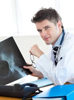 Chirurgo bello che analizza i raggi x con un paziente femminile