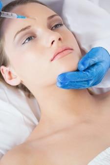 Chirurgo che fa iniezione sulla fronte sulla donna rilassata che si trova