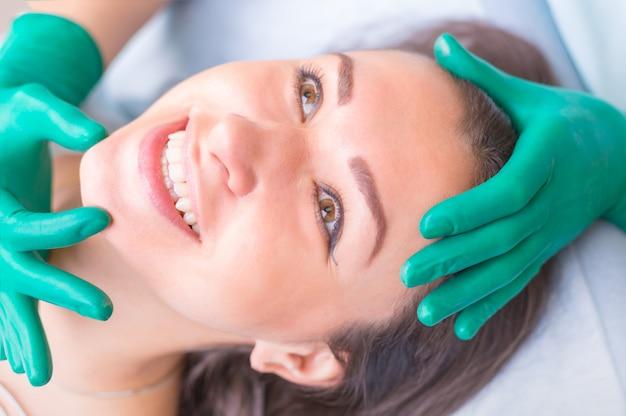 Chirurgo estetico che esamina cliente femminile nel clinik prima di plast