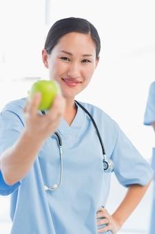 Chirurgo femminile sorridente che dà una mela in ospedale