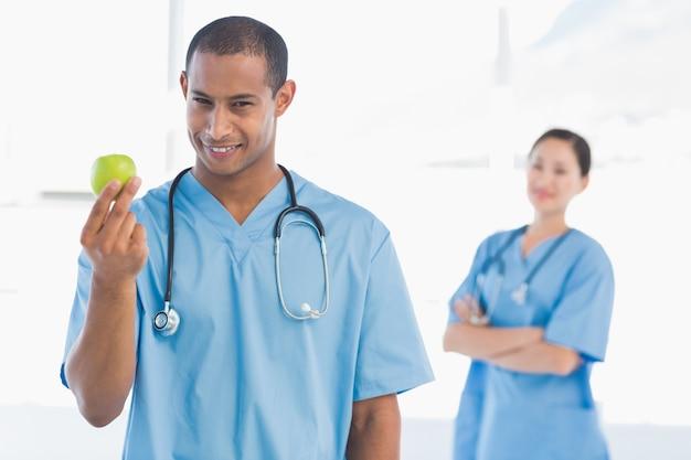 Chirurgo maschio che tiene una mela con il collega dietro