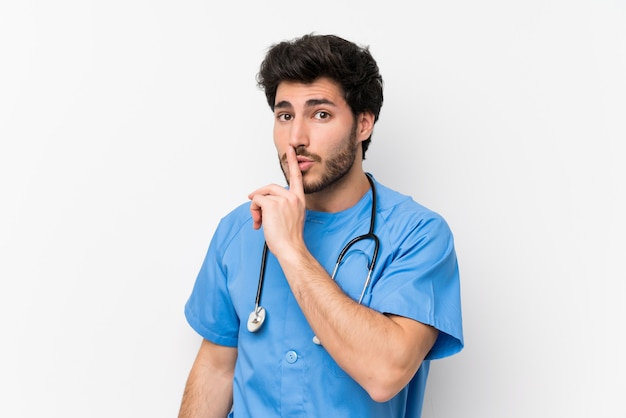 Chirurgo medico uomo sopra muro bianco isolato facendo gesto di silenzio