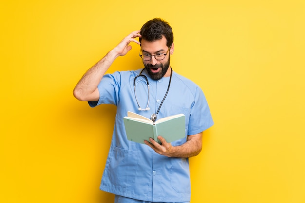 Chirurgo medico uomo sorpreso mentre si diverte a leggere un libro