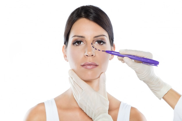 Chirurgo plastico che disegna linee tratteggiate sul viso della sua paziente.