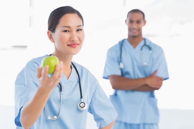 Chirurgo sorridente che tiene una mela con il collega in ospedale