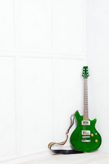 Chitarra appoggiata davanti a un muro bianco