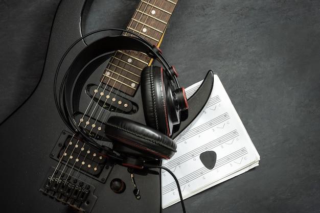 Chitarra elettrica nera e cuffia sul pavimento.