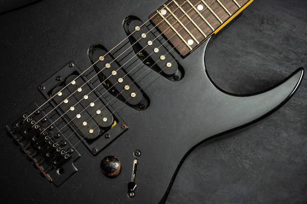 Chitarra elettrica nera sul pavimento di cemento nero. vista dall'alto e spazio di copia. concetto di musica rock.
