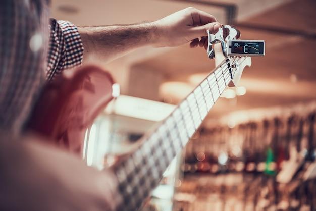Chitarrista accorda la chitarra con la clip di sintonizzatore, pioli di torcimento.